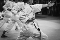 Kids training on karate-do.  Black and white. Photo without faces.Simulating the grain of film photography.