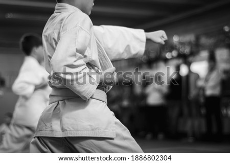 Kids training on karate-do.  Direct punch training. Sports training and a healthy lifestyle.  Black and white  Photo without faces. (focus on the shape on the left. On the right, space for text) Foto stock ©