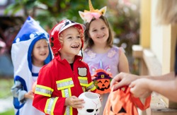 Kids trick or treat in Halloween costume. Children in colorful dress up with candy bucket on suburban street. Little boy and girl trick or treating with pumpkin lantern. Autumn holiday fun.