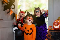 Kids trick or treat on Halloween night. Child at decorated house door. Boy and girl in witch and vampire costume and hat with candy bucket and pumpkin lantern. Autumn decoration. Friends play.