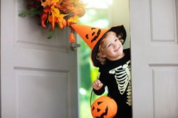 Kids trick or treat on Halloween night. Child at decorated house door with autumn leaf wreath and pumpkin lantern. Little boy in witch and skeleton costume and hat with candy bucket. Fall decoration.