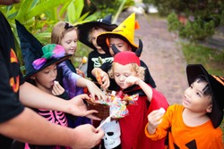 Kids trick or treat on Halloween night. Mixed race Asian and Caucasian children at decorated house door. Boy and girl in witch and vampire costume and hat with candy bucket and pumpkin lantern.