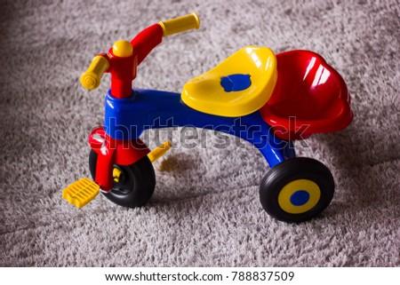 kids tricycle on grey carpet