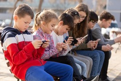 Kids using phones outdoors, concept of children addiction to social network