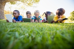 Kids using technology during a sunny day at park