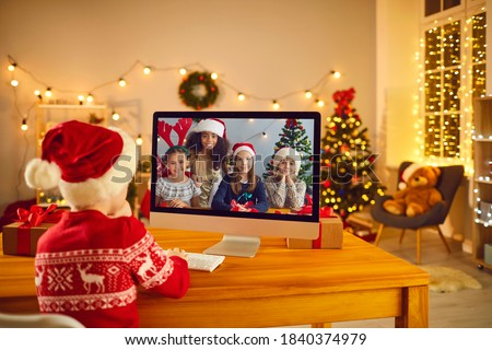 Kids video calling each other to stay in touch on winter break. Little boy in Santa hat sitting in front of computer screen, chatting online with group of his diverse friends on Christmas Eve at home