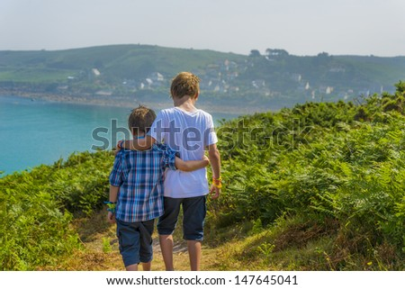 kids walking towards the sea, at a beautiful bay in normandy.