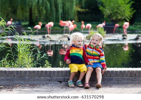 Kids watch animals and birds at the zoo. Children watching wild life at safari park. Family day feeding animal at city zoo or farm. Boy and girl exploring nature and wildlife. Summer day trip. #631570298