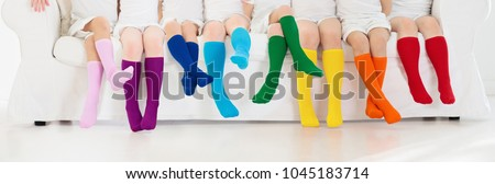 Kids wearing colorful rainbow socks. Children footwear collection. Variety of knitted knee high socks and tights. Child clothing and apparel. Kid fashion. Legs and feet of little boy and girl group. - Shutterstock ID 1045183714