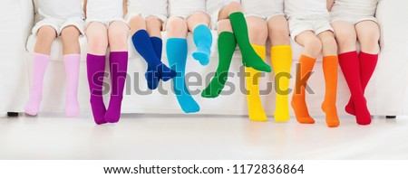 Kids wearing colorful rainbow socks. Children footwear collection. Variety of knitted knee high socks and tights. Child clothing and apparel. Kid fashion. Legs and feet of little boy and girl group.