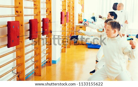 Kids with adults practicing effective techniques of fencing in training room