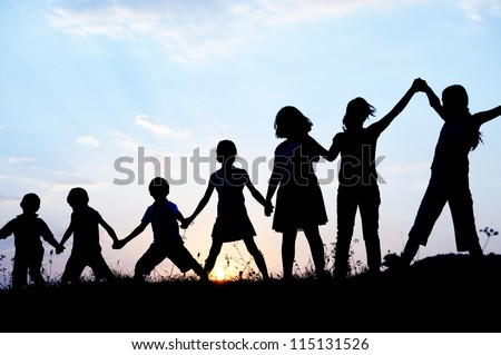 Kids with arms up together in nature
