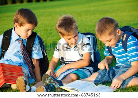 Kids with books sitting in park