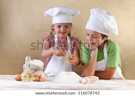 Kids with chef hats preparing the cake dough - mixing ingredients