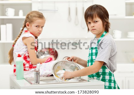 Kids with grumpy faces because they have to do the dishes by themselves