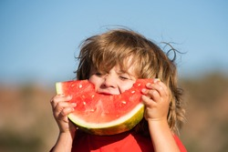 Kids with hungry face eating red watermelon in mouth. Child eat melon