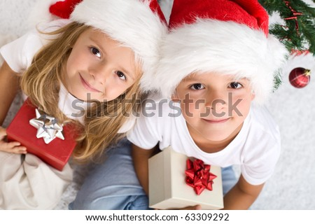 Kids with their christmas presents presents sitting on the floor