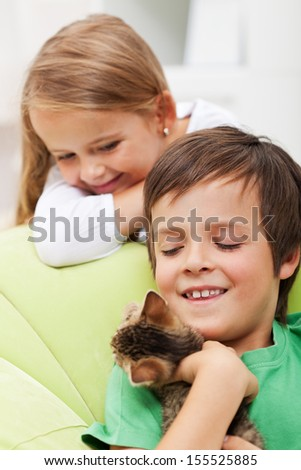 Kids with their new pet - a playful kitten
