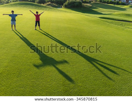 Kids with their shadows on grass