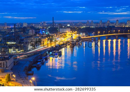 Kiev, Capital of Ukraine. View of the Dnieper River, River station and the historic district of Podil. Night panorama of Kyiv.