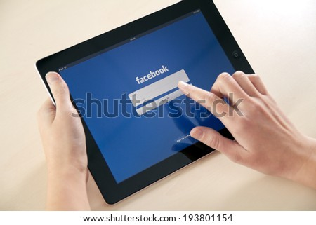 KIEV, UKRAINE - DECEMBER 03, 2011: A girl trying to log in Facebook application using Apple iPad. Facebook is largest and most popular social networking site in the world.