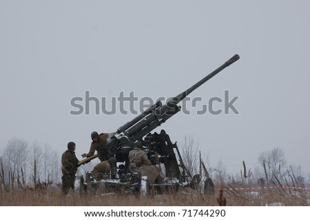 KIEV, UKRAINE - FEB 20: Members of military history club wear historical Soviet uniform& air defense cannon during historical reenactment of WWII,,February 20, 2011 in Kiev, Ukraine