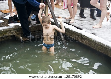 KIEV, UKRAINE - JAN 19: unidentified little boy dive in the hole in the cold water in the feast of the Epiphany January 19, 2013 in Kiev, Ukraine
