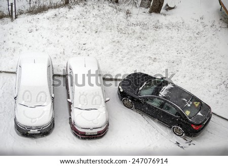 KIEV, UKRAINE - January 22, 2015: Funny faces drawn on the snow on the windshield of the car parked in the courtyard of a condo. In Ukraine is rainy-snowy day.