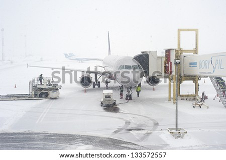 KIEV, UKRAINE - JANUARY 12: Unidentified workers preparing an airplane during the snowfall on January 12, 2013 in Kiev, Ukraine. Kiev was covered by 20 inches of snow, the largest amount since 1889