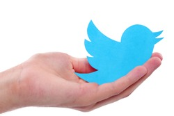 KIEV, UKRAINE - JULY 8, 2015: Hand holds twitter logotype bird printed on paper. Twitter is an online social networking service.