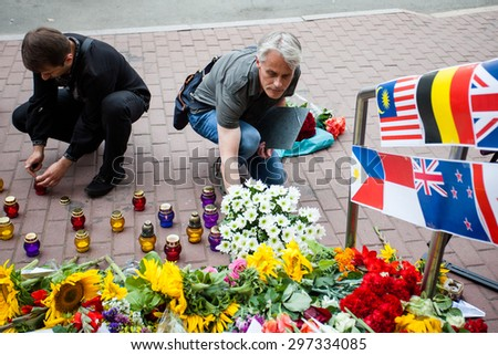 Kiev, Ukraine -  17 July 2015: People place flowers and light candles in commemoration of the victims of Malaysia Airlines MH17 plane accident in eastern Ukraine, in front of the Dutch embassy