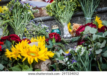 Kiev, Ukraine -  17 July 2015: People place flowers,  toys and light candles in commemoration of the victims of Malaysia Airlines MH17 plane accident in eastern Ukraine, in front of the Dutch embassy