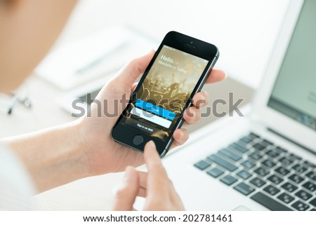 KIEV, UKRAINE - JUNE 27, 2014: Person holding a new Apple iPhone 5S with Twitter app login page on the screen. Twitter is a social media online service for microblogging and networking communication.