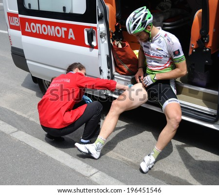 KIEV, UKRAINE - 1 JUNE 2014: Unknown doctor gives a medical help to unknown cyclist after road accident on June 1, 2014 in Kiev, Ukraine.