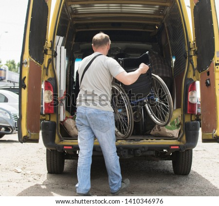 Kiev, Ukraine- May 18, 2019: loading wheelchairs into a minibus for transportation #1410346976