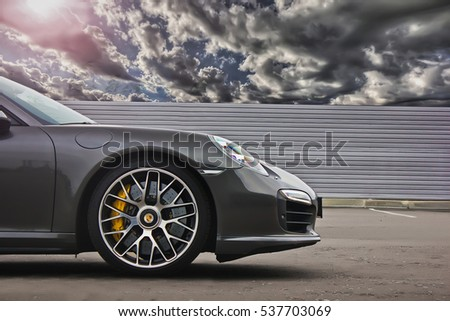 Kiev, Ukraine; October 17, 2016; Porsche 911 Turbo S (991) (2016) on a background of cloudy sky. Beautiful rainy sky. Hurricane. Editorial photo.