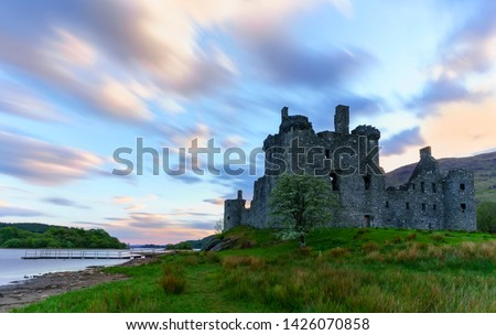 Kilchurn Castle , in the care of Historic Environment Scotland , is a ruined structure on a rocky peninsula at Loch Awe in twilight , Argyll and Bute, Scotland #1426070858