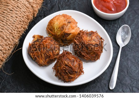 Kilikoodu or birds nest hot and spicy savoury Malabar snack with tomato sauce or ketchup for iftar party, Kozhikode Kerala India. Egg stuffed balls.