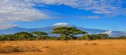 Kilimanjaro mountain Tanzania snow capped under cloudy blue skies captured whist on safari in Africa Kenya.