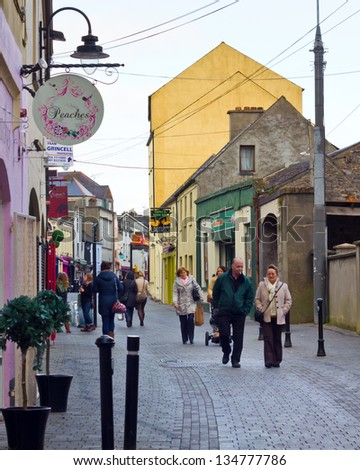 KILKENNY, IRELAND - MAR 28:  Pedestrians on scenic street in Kilkenny Ireland on Mar. 28, 2013.  This medieval walled city was founded in 1207 and is now a popular tourist destination. - stock photo