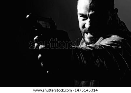 Killer or murderer concept. Mafia killer going to shot someone. Finish him. Kill them all. Final shot. Concentrate on gun shot. Need for revenge. Close up gun barrel.