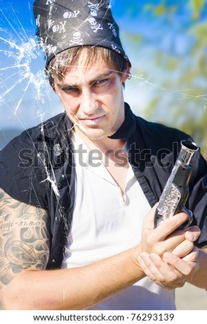 Killer Pirate Holding A Hand Gun Or Pistol Looks Through A Bullet Hole In A Fractured And Ruptured Pane Of Glass During An Assassination Killing Or Murder