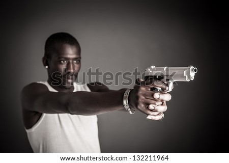 Killer with gun close up over dark background. Focus on gun. - stock photo