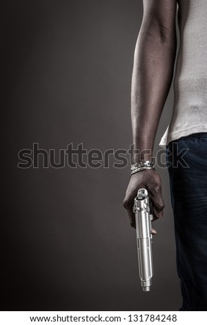 Killer with gun close up over dark background with copyspace.