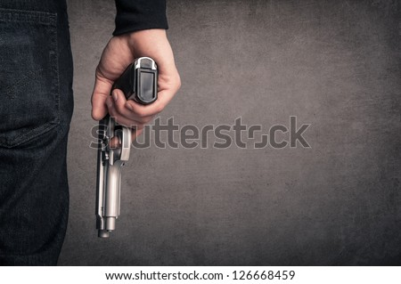 Killer with gun close up over grunge background with copyspace.