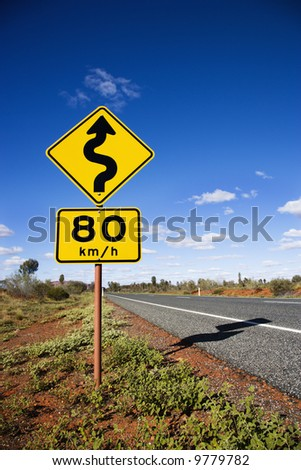 Kilometer per hour speed limit and curve ahead road signs in rural Australia.