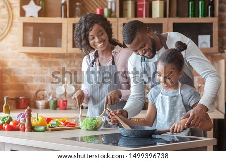 Kind african parents teaching their adorable daughter how to cook healthy food, free space
