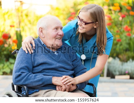 Kind doctor taking care of an old man in wheelchair.