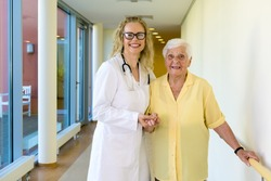 Kind Female Nurse Assisting her Old Woman Patient at the Hallway in the Hospital, Smiling at the Camera