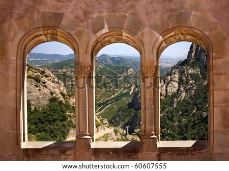 Kind from arch windows of a monastery of Montserrat on a valley